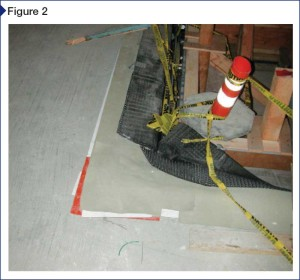 The waterproofing system consists of a felt leveling layer placed over the structural slab with a loose-laid thermoplastic waterproofing sheet, oil containment sheet, and protection layer over the felt layer. Over this is a prefabricated composite drainage panel, comprising a three-dimensional high-strength and impact-resistant polypropylene core with a woven geotextile fabric bonded to the top side.