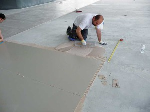 In the photo above, large-format thin tile being installed over concrete.