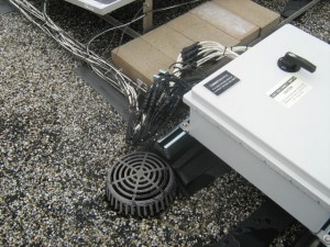 Ballasted, non-penetrating PV system and wiring located near a roof drain.