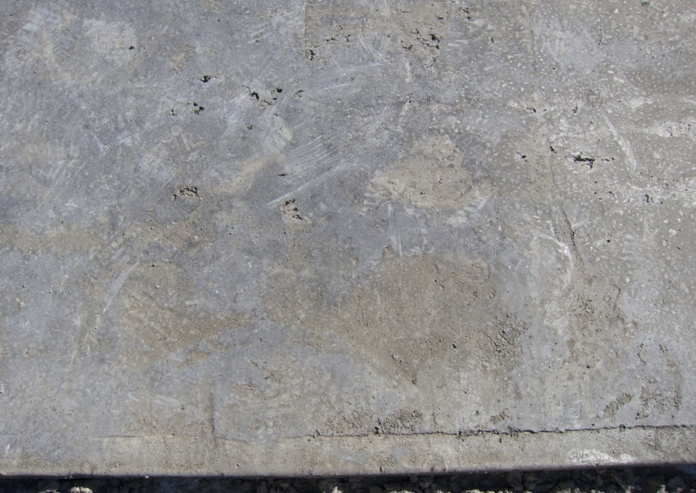 Finishers refer to this as 'losing the slab.' Hot conditions speed up the set-time of the cement, and moisture loss deprives the finisher of enough fluid cement paste to cover the interstices between the coarse aggregate ('closing' the surface). The result is a porous, rough slab with many surface defects.