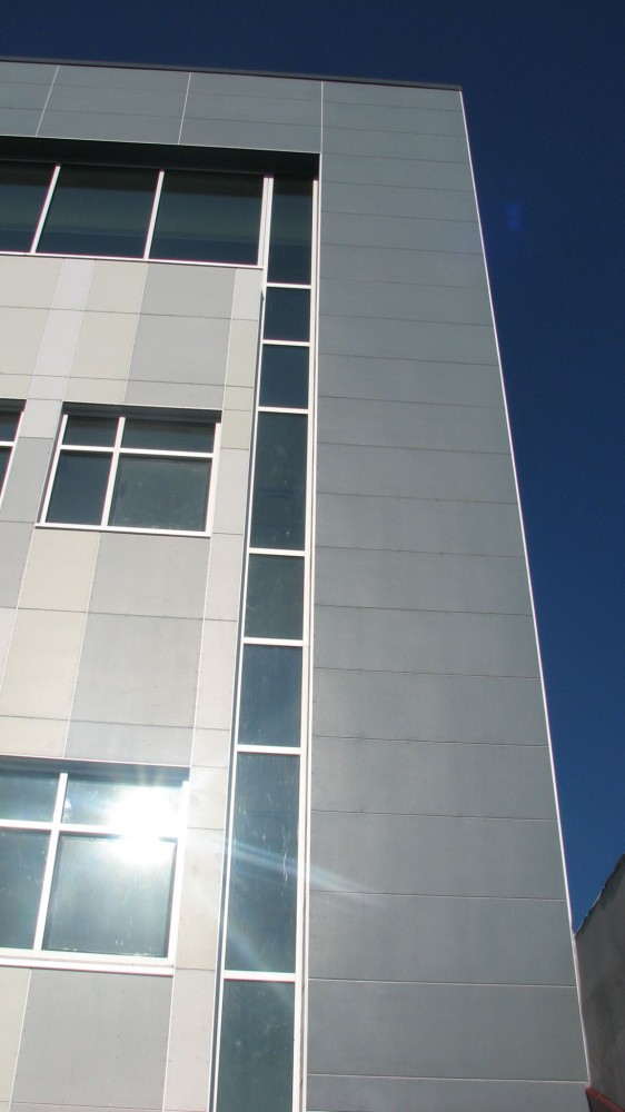 Fiber cement siding can be more durable than vinyl or wood for withstanding impacts from ice, hail, or storm debris. This image shows fiber cement siding on Lighthouse High School in the Bronx, New York.
