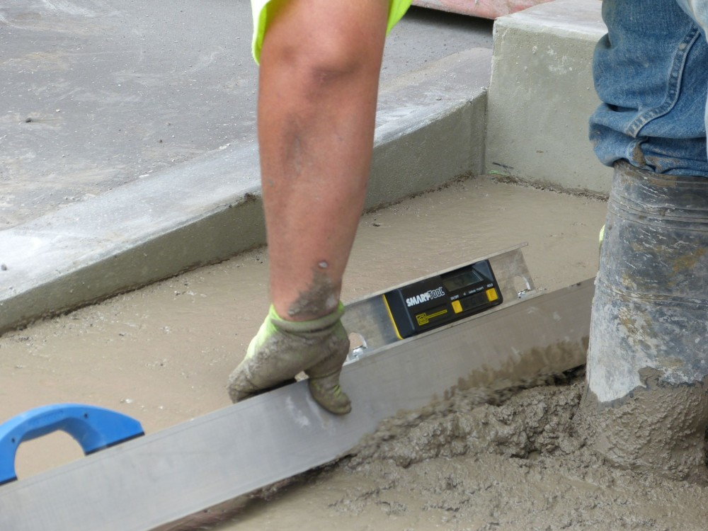 Initial screeding: second-phase bump-cutting using a digital level mounted on a mag beam screed.