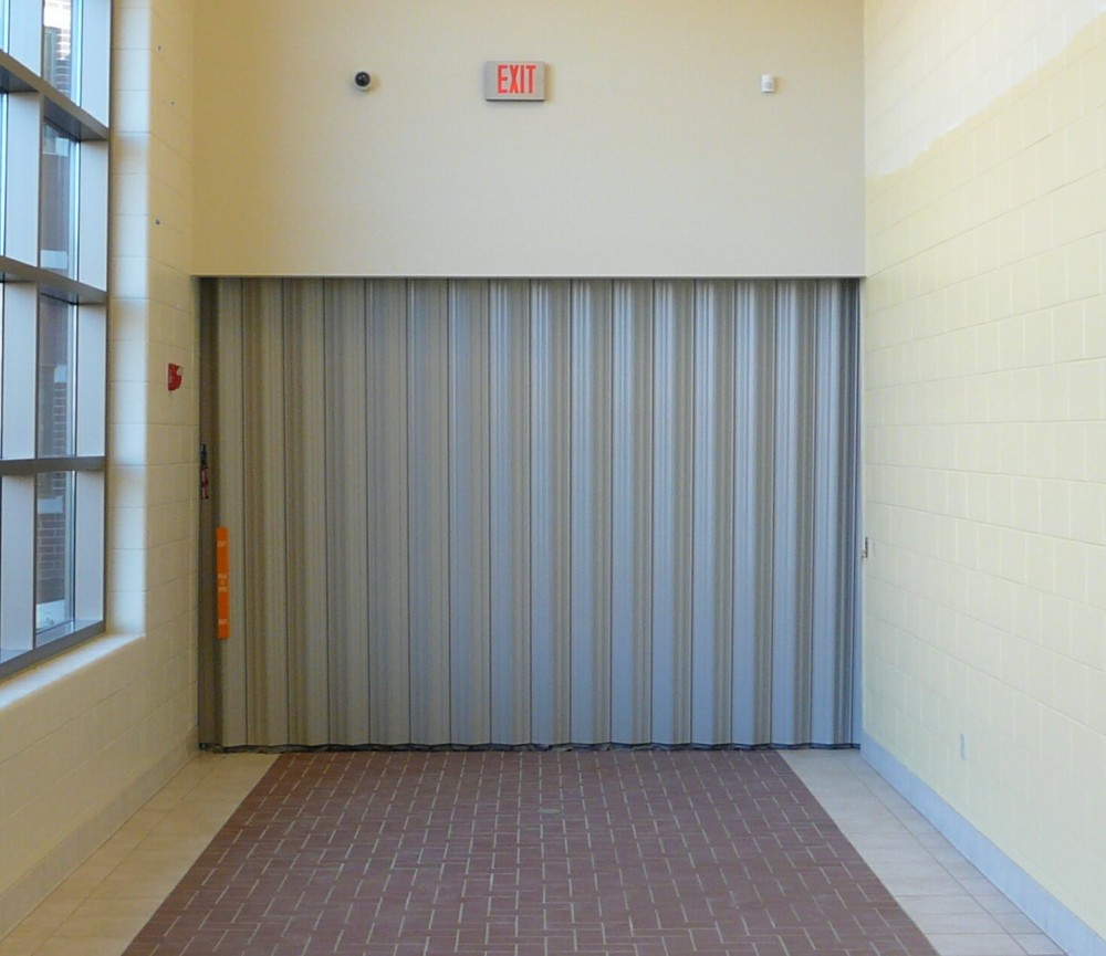 Accordion partitions may be used to create a physical barrier across corridors, yet also allow emergency egress when required.