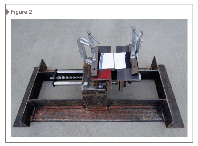 A bench vise was modified by welding steel angles to make a frame, and the handle was replaced with a socket to allow smooth opening of the jaws. Coating was applied to a vinyl test substrate and clamped under bars on the jaws.