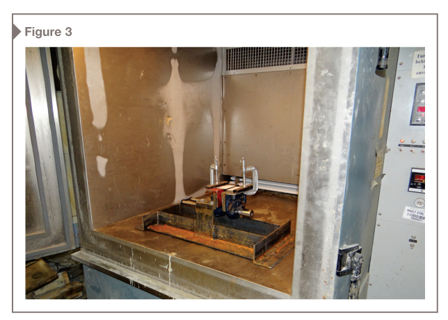 The testing apparatus was designed to fit into a standard chest freezer, but an environmental chamber is used at the lab.