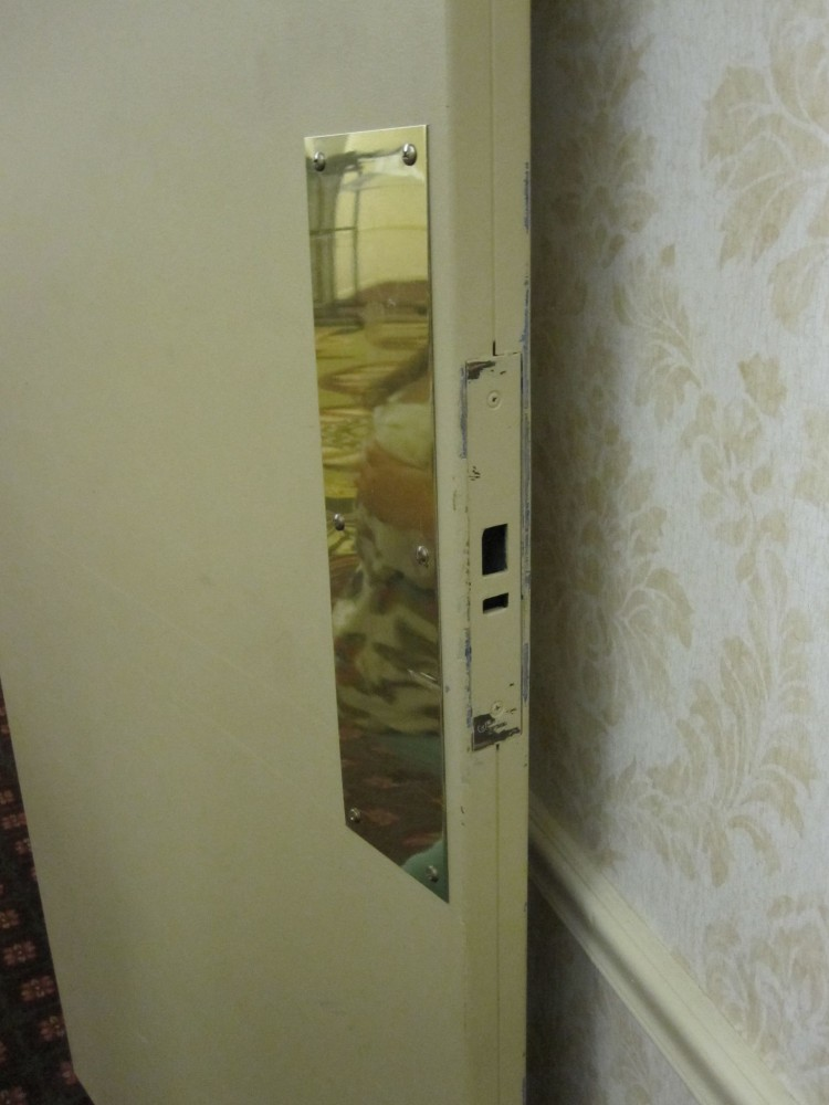 Fire doors are typically required to latch, but defective latching hardware is sometimes removed instead of replaced, as illustrated in this photo of an existing fire door in a hotel corridor.