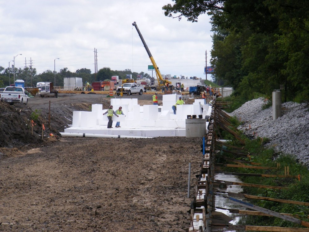 Highway construction crews place EPS geofoam blocks to remediate soft soils in this Indiana freeway interchange.