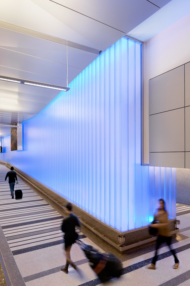 An airport partition wall at Los Angeles International Airport's (LAX's) Tom Bradley International Terminal with interior neon lighting alternates colors to connect travelers to the city's vibrant culture. [CREDIT] Photo courtesy Technical Glass Products