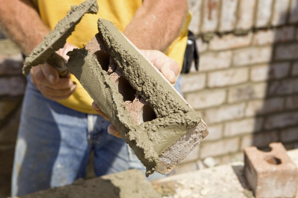At left, a mason 'butters' a brick with mortar for installation in a masonry cavity wall. In the photo on the right, one can see the detail of a masonry cavity wall comprising a concrete-unit structural wall and brick veneer.