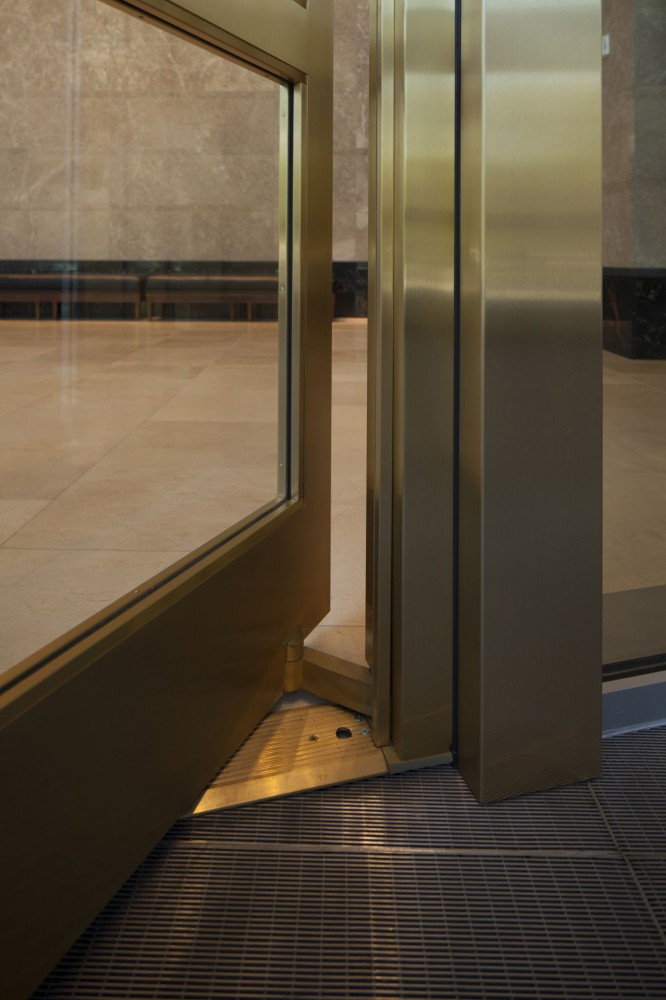 A balanced door pivots at two-thirds of the door, distributing the weight and creating a balance allowing the door to easily open. The bottom arm (shown above) is one of two connections between the door leaf and frame. One end of the bottom arm is connected to the door by a stainless steel pin which projects out of the door bottom pivot and engages into the arm. The other end of the bottom arm is welded to the full-height steel tube portion of the hinge pivot assembly.  [CREDIT] Photo © Heather Collins Roe Photography
