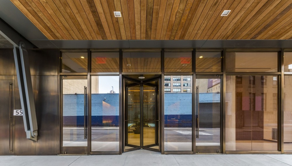 Gotham West, a luxury rental apartment building in New York City, facilitates access with two single narrow stile bronze balanced door units with a satin finish. The narrow stile design features tempered glass construction, containing a top and bottom rail that secures the glass to the hinging mechanism. [CREDIT] Photo © Barry Schwartz Photography