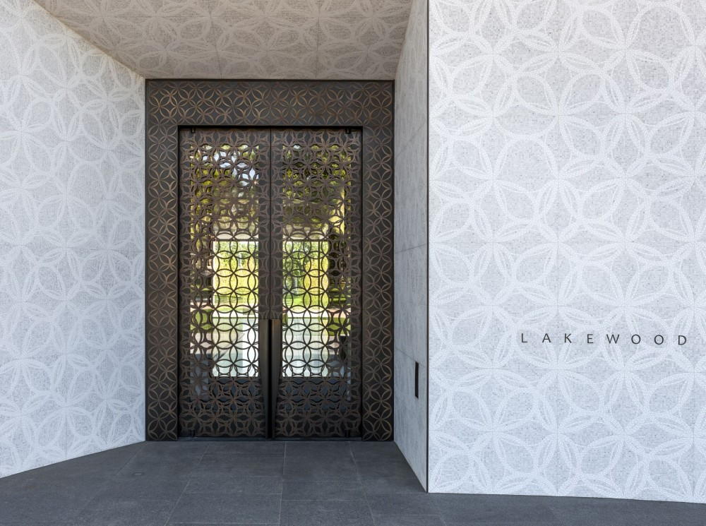 The main entrance of the Lakewood Cemetery's Garden Mausoleum in Minneapolis showcases a pair of custom muntz-bronze balanced doors covered in decorative bronze grilles with a wide perimeter accent bronze trim. [CREDIT] Photo © Paul Crosby