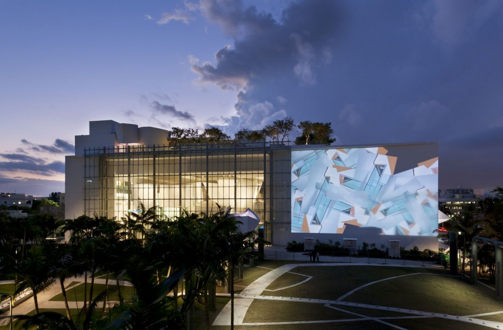 An evening view of the New World Center, featuring The Wall (a 650-m2 [7000-sf] projection wall) and SoundScape (a 1-ha [2.5-acre] multiuse urban space).