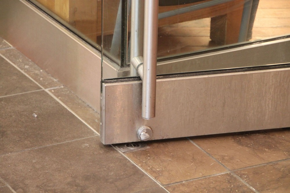 Manual doors on an accessible route must have a smooth surface on the push side with no protruding hardware within 254 mm (10 in.) of the floor or ground. In the photo at left, these components could inhibit passage through a door opening by catching a crutch, cane, walker, or wheelchair.