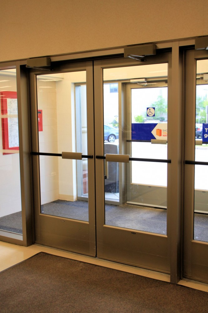 Manual doors on an accessible route must have a smooth surface on the push side with no protruding hardware within 254 mm (10 in.) of the fl oor or ground. In the photo at left, these components could inhibit passage through a door opening by catching a crutch, cane, walker, or wheelchair.