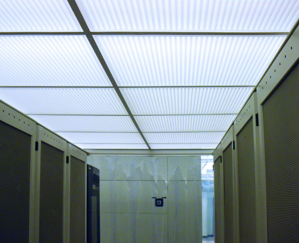 Computer server farms illustrate how thermoformed ceiling products can solve a complex set of requirements. Cool air is typically fed into server racks to keep equipment within an optimal operating temperature range. Instead of releasing heated air into the surrounding room, aisles between racks are enclosed to act as plenums for exhaust air. By using translucent, drop-out panels as above-aisle ceilings, light fixtures and fire sprinklers can be located above server banks where they will not interfere with access to servers.