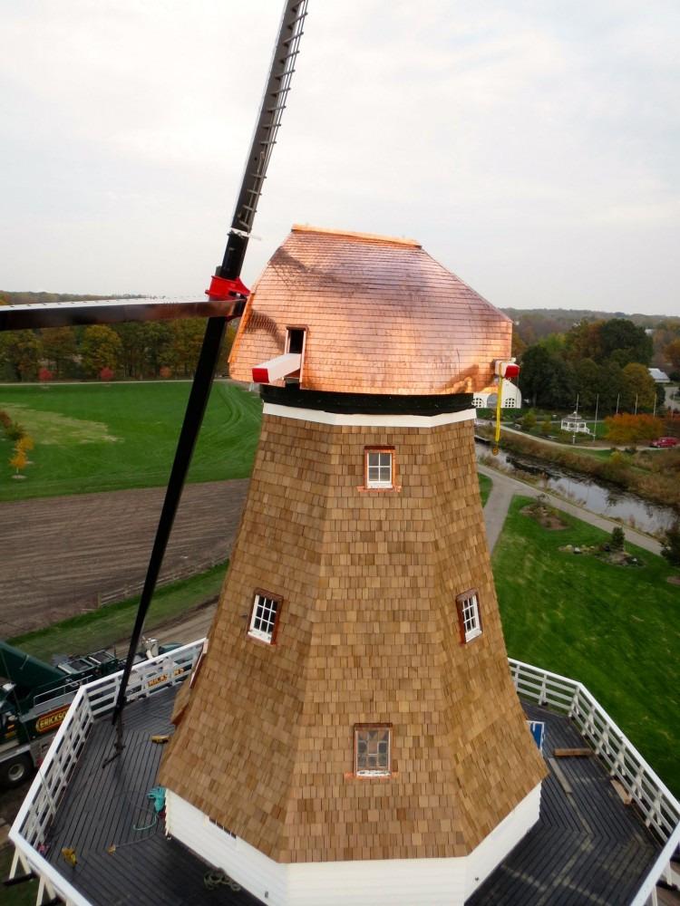 Moved decades ago from Holland (Netherlands) to Holland (Michigan), this 18th century windmill has a cap covered by nearly 2260 kg (5000 lb) of sheet copper, individually cut and hemmed from 20-oz. sheet copper before being secured with brass screws. In many cases, the uniquely curved shape of the cap required shingles be rolled by hand to ensure they lay flat against the roof contours. Photo © Brian Blank