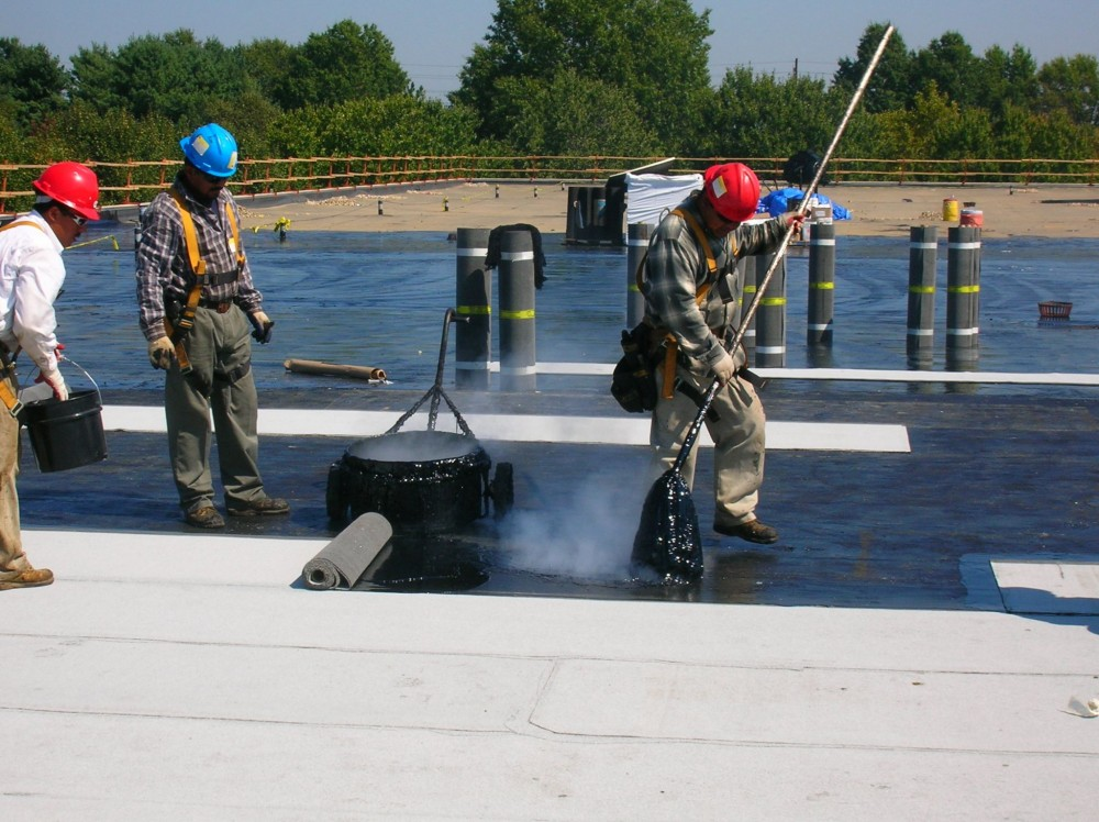 A fully adhered modifi ed-bitumen (mod-bit) membrane is being installed with hot asphalt. The worker at the left is 'sugaring' loose granules into the asphalt at seams to produce a uniform refl ective fi nish.