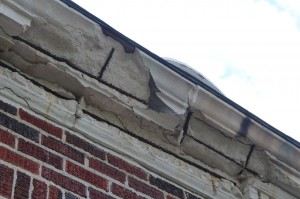 The cast stone cornice on this 1920s building is severely deteriorated due to water infiltration through open joints and cracks, and corrosion of steel reinforcement. The dark gray area is a failed cementitious patch. Photos courtesy Kenneth M. Itle