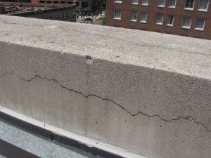 This cast stone coping on a 1990s building exhibits significant cracking attributed to water infiltration, corrosion of embedded steel, and cyclic freezing and thawing.