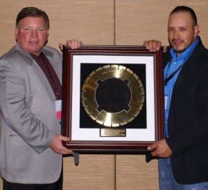 Tomas Ramos, project supervisor at Concrete Stabilization Technologies, receives the 2014 Operator of the Year (Iron Man) Award from Roberts.