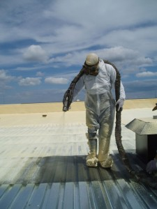 The sprayfoam installer for a roofing application is shown in full personal protective equipment.