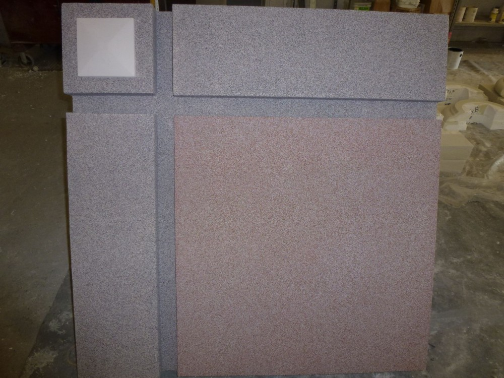 Two different EIFS finishes are displayed here. The small medallion in the left corner shows a smooth finish to replicate limestone. The finish in the rest of the sample is shown in gray and and a contrasting red color. This finish consists of a ceramic bead in a clear acrylic binder for abuse resistant interior and exterior applications. Photo courtesy Southern Stucco