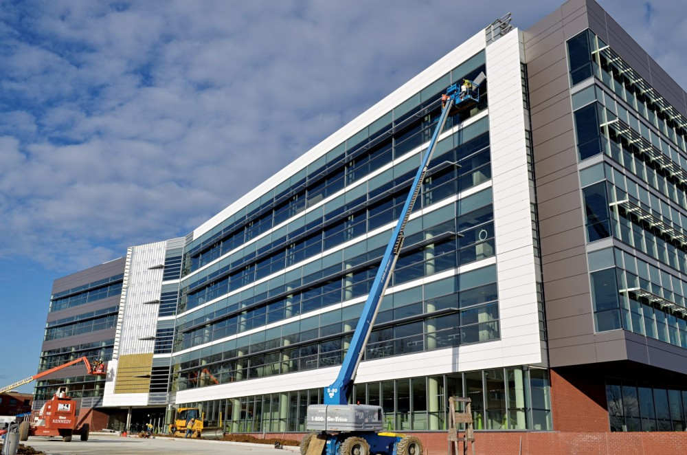 A properly installed building wrap air and water barrier system is the most cost-effective option for this building with sheathing substrate and multi-story curtain wall consisting of brick and solid-surface cladding panels.