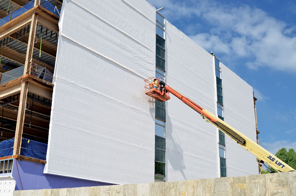 A building wrap air and water barrier system is installed over the exterior sheathing, prior to the installation of metal panels. Proper installation is critical for meeting the building envelope structural wind loads and maintaining the air barrier continuity over time.