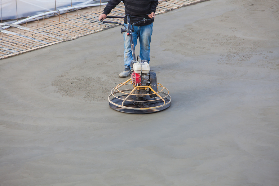 Construction worker produces the grout and finish wet concrete with a special tool. Float blades. For smoothing and polishing concrete, concrete floors ** Note: Shallow depth of field