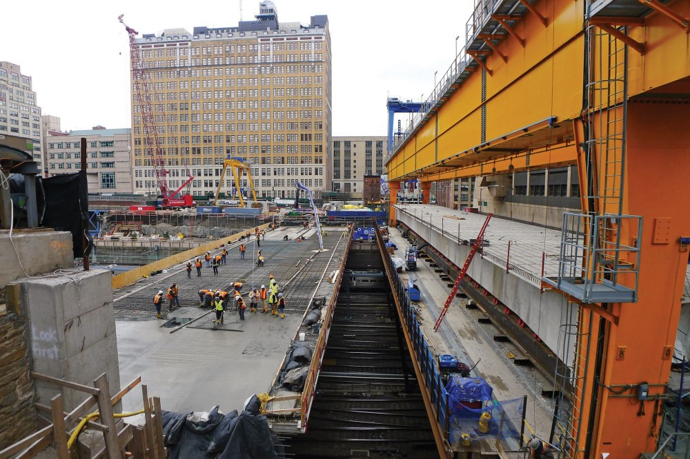 Overlooking the site for the 650,320-m2 (7 million-sf) Manhattan West mixed-use development project located in the Hudson Yards District, the platform takes shape with Spans 1 through 3 already erected, and Span 4 being assembled under the launcher (left). Above, bonded topping slab concrete is being poured over Spans 3 and 4.