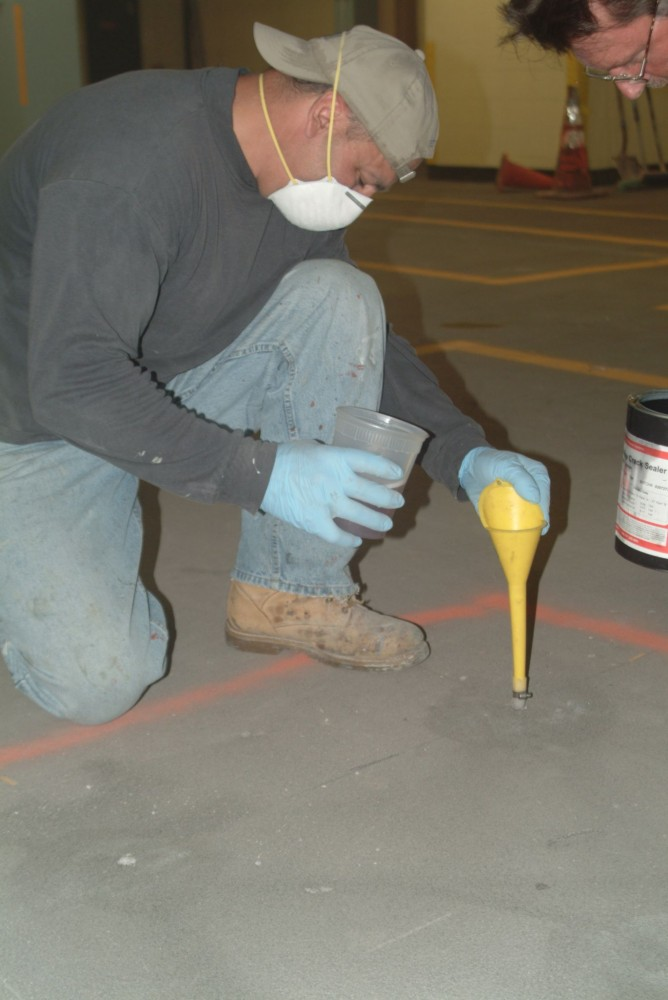 Gravity-feeding an epoxy healer/sealer can repair cracks on a concrete deck.