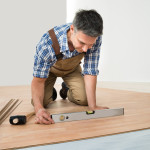 Carpenter Installing New Laminated Wooden Floor At Home