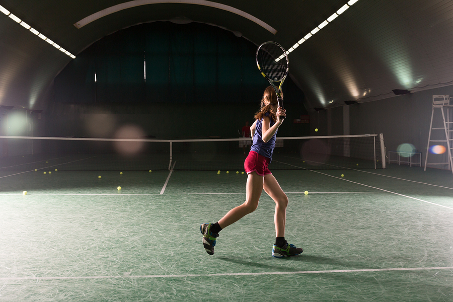 Young girl playing tennis at indoor court