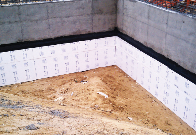 A layer of foam insulation helps protect the water proofing on foundation walls during backfill.