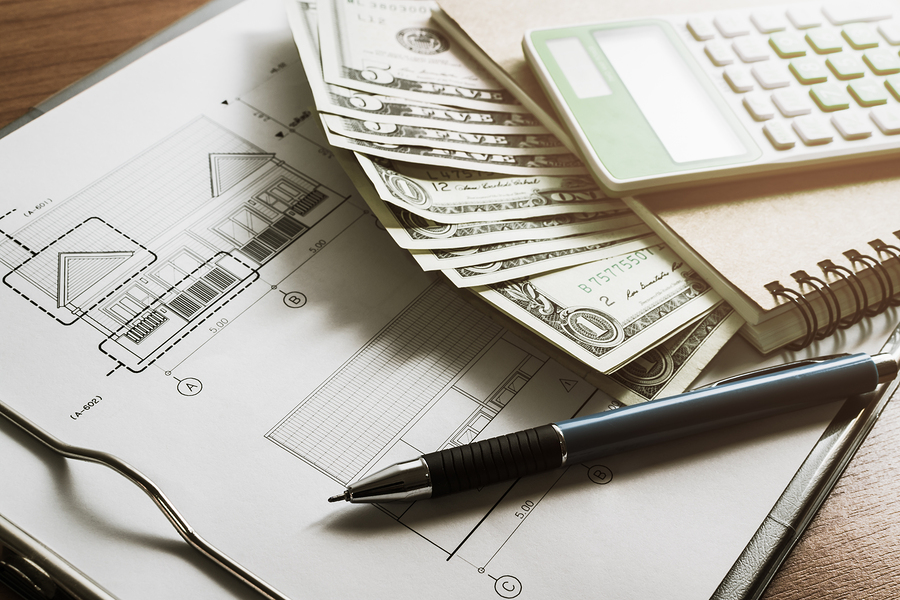Investment for construction with limit budget Construction plan pen money notebook and calculator on wooden table