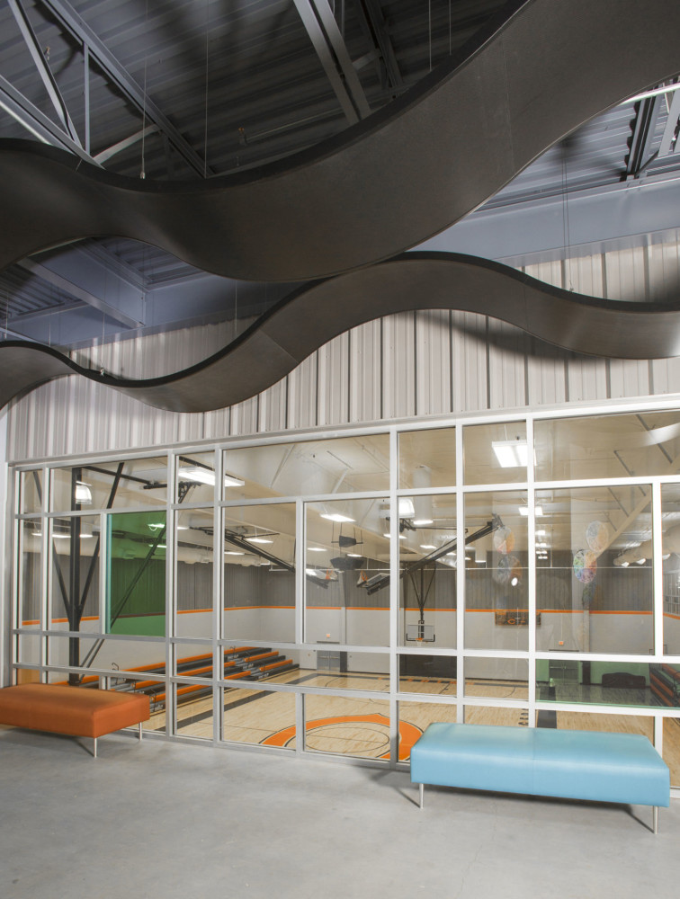 The new Cushing Middle School in Oklahoma features curved aluminum ceiling panels to create interest and to help promote quiet, comfortable learning spaces. Photos courtesy Rockfon. Photos by Miller Photography Inc.