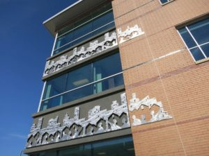 Original artwork on the building's façade depicts abstract human figures holding hands in the foreground with houses and urban cityscapes behind them, symbolizing Continuum's core values of 'home' and 'community.' Photo courtesy Svigals + Partners