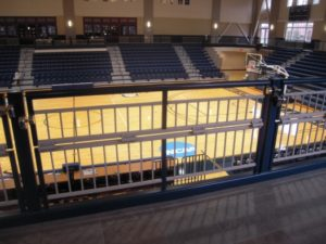 A guardrail at Berry College is locked in an upright position for safety, and folds in half for a wheelchair patron. Seats underneath the rail are lower to prevent obstructed view when standing.