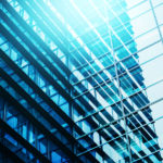Modern Business Office Building Windows Repeating Pattern Blue Glass Facade with Geometric Lines Sunlight Reflecting