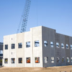 Large panels of precast concrete are tilted up with cranes to form the walls of a large building