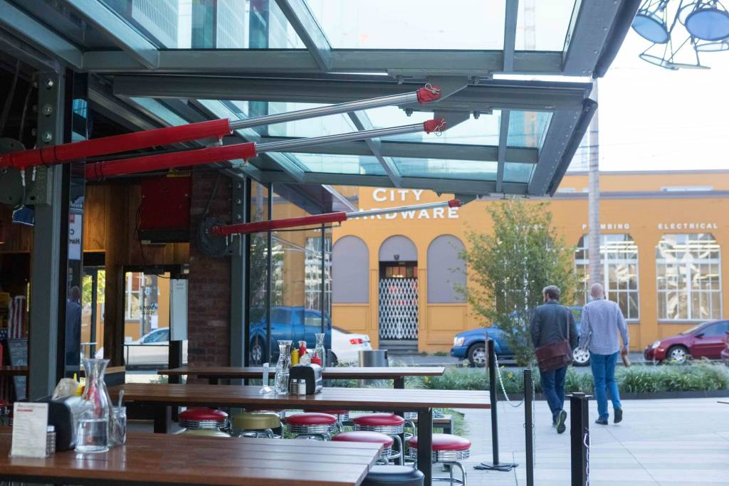 The Glass Clad Hydraulic Doors At Samu0027s Tavern Provide A Protective Canopy  For Outside Diners. Photos © Schweiss Doors