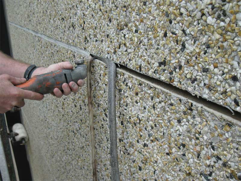 Façade sealant replacement begins with complete removal of existing sealant and backer rod.