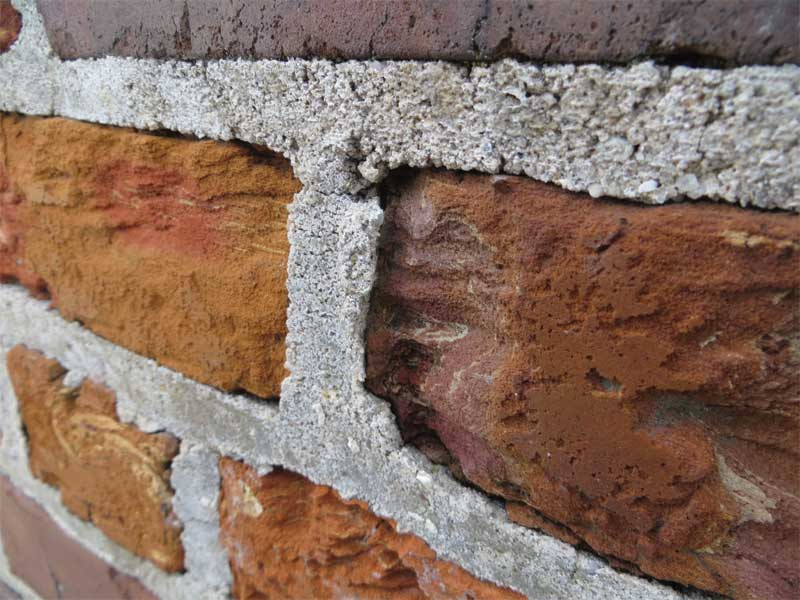 The exterior brick masonry exhibits surface erosion of the red/orange brick, revealing the unusual internal structure. The mortar is relatively hard and projects above the eroded surface of the adjacent brick units. Photos © David Patterson and Hugh Hou of WJE