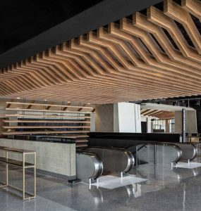 A custom-designed shelf wall fits above the escalators to define a main entrance to the facility and extend the wood ceiling aesthetic.