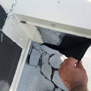Failed flashing and roofing patches at an interior corner.