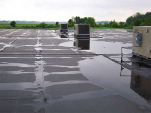 Figure 5: Pull-back view of water trapped between RTUs looking east. Note the lack of a roof drain and/or a well-defined waterway. Ponded water can also be observed in the background.