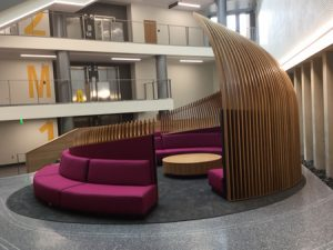 More than 100 custom wood 'ribs' rise straight up immediately behind the large half-circle upholstered seats and gradually start to roll in and converge overhead toward a center point.