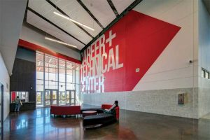 The Arlington Independent School District's Dan Dipert Career + Technical Center in Texas showcases its school colors throughout its exterior. The aluminum panels are finished using 70 percent polyvinylidene fluoride (PVDF) coatings in gray and three custom reds, as well as clear anodize. Photo © Chad M. Davis, AIA, NCARB, LEED AP. Photo courtesy Linetec and Tubelite Inc.