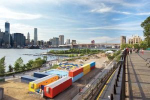 Spacesmith with partner firm Davis Brody Bond transformed a riverside stretch into a pop-up pool in Brooklyn, New York. Shipping containers painted in bold, primary colors were repurposed as storage space. They also act as a buffer to the noise of a nearby expressway.